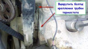 Выкрутить болты крепления трубки термостата
